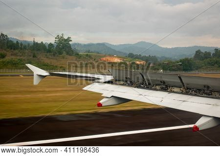 Bogota, Colombia - February 25 2021: Plane Wing During Takeoff Over The Runway With Fertile Yellow L