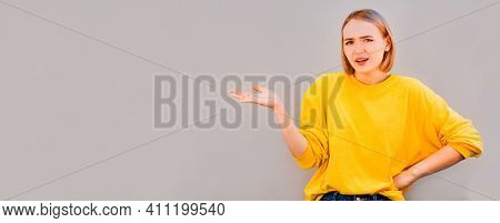 Close Up Of An Attractive Young Woman With A Horrified Expression Clenching Her Hands In Frustration