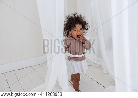 Little Curly African American Girl Has Fun Laughs Dances Among Airy White Tulles Fabric. Minimalist