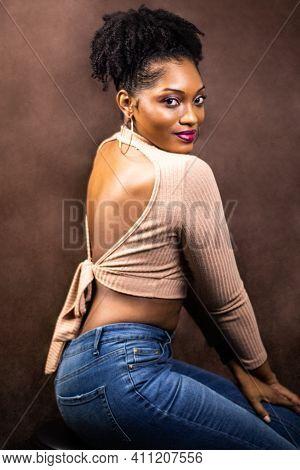 Black Woman Posing In A Brown Sweater