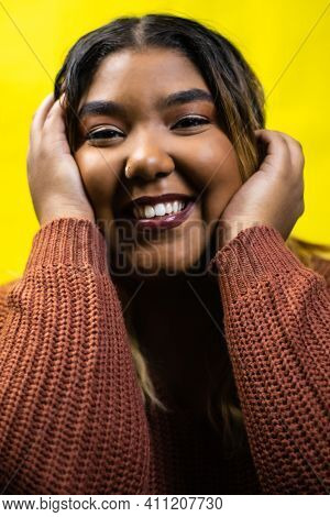 Black Woman Smiles With Her Hands On Her Face