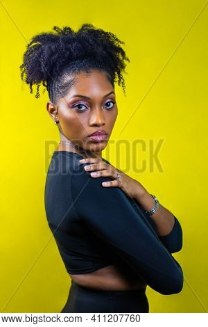 Black Woman With Natural Hair Poses With Her Hand On Her Shoulder, Black Woman Wearing Silver Jewelr