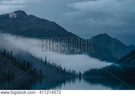 Low Cloud Above Highland Lake. Silhouettes Of Trees On Hillside Along Mountain Lake In Dense Fog. Re