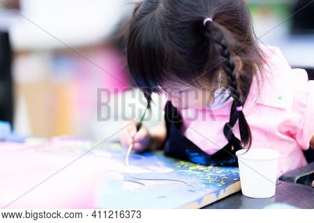 Child Do Art On Canvas In The Classroom. Children Paint The Watercolor In Class With Great Intention