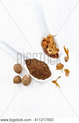 Nutmeg Round And Mace In Spoons On White Board Top