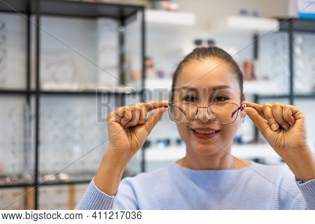 Selective Focus At Glasses. Senior Elder Asian Women Smile And Look At The Mirror While Choosing Bea