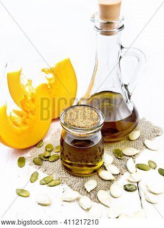 Oil Pumpkin In Jar And Carafe On Light Board