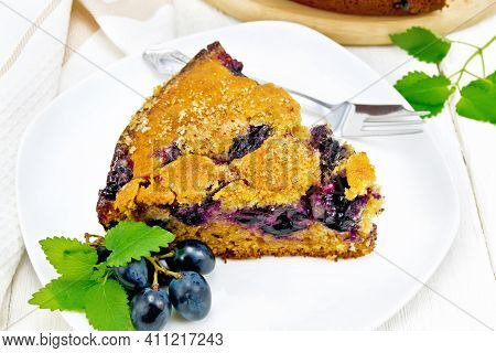 Pie With Black Grapes  In Plate On Wooden Board