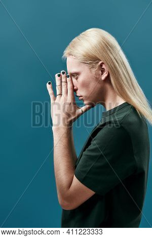 Young Caucasian Man With Long Fair Hair Holding Manicured Hands In Praying Gesture While Posing On B