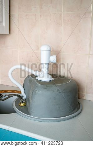 Process Of Installing A Stone Sink In The Countertop In The Kitchen. The Sink With Plumbing Accessor