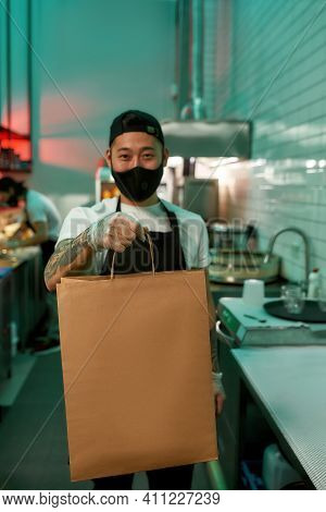 Restaurant Chef Standing With A Package In His Hand. Young Man Standing In A Restaurant With A Packa