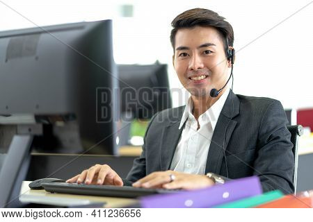 Young Handsome Male Customer Support Phone Operator With Headset Working In Call Center. Professiona