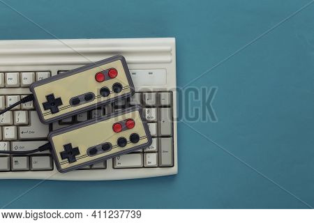 Old Keyboard And Old-fashioned Gamepads On A Blue Background. Retro Gaming. 80s. Top View. Flat Lay