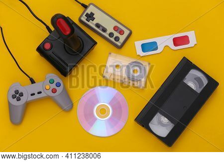Flat Lay 80s Attribute Composition. Gamepads, Audio And Video Tapes, Cd, 3d Glasses. Retro Electroni