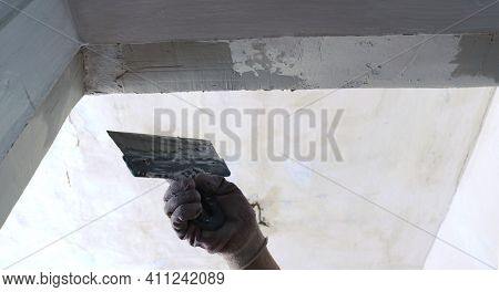 The Hand Of A Plasterer In A Glove With A Spatula Smoothes The Narrow Surface Of The Doorway In A Ro