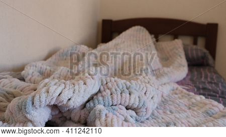 A Cozy Hand-knitted Blanket Made Of Soft White-pink Wool Is Casually Crumpled On A Wooden Bed In A R