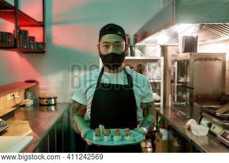Young Man In Black Mask Holding Delicious Sushi In Hands. Asian Restaurant Chef With A Dish In His H