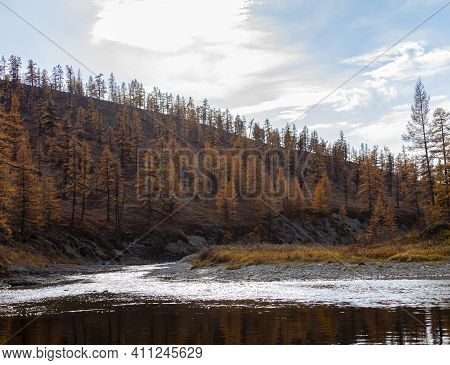 Landscape On The Siberian River With Background Of Cloudy Sky And The Shore With Larch Autumn Taiga.