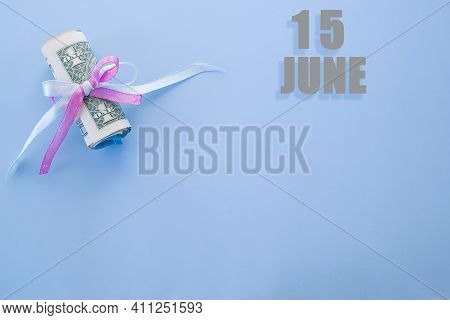 Calendar Date On Blue Background With Rolled Up Dollar Bills Pinned By Blue And Pink Ribbon With Cop