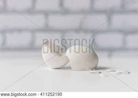 White Eggshell Of A Broken Chicken Egg With Shards Isolated On A White Background. White Brick Wall