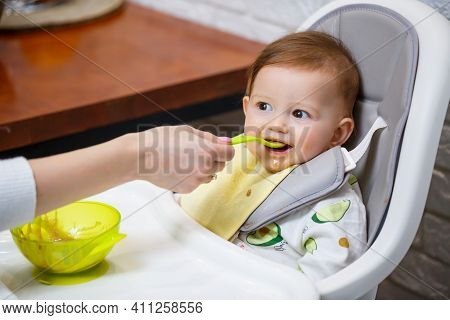 A Nine Month Old Smiling Baby Sits At A White Table In A Highchair And Eats With A Spoon From A Bowl