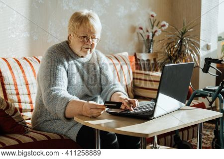 Senior Woman Holding Credit Card Near Laptop At Home. Mature Woman Shopping Online, Using Credit Car