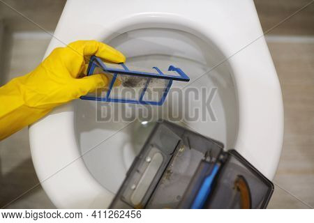 Hands In Protective Rubber Gloves Throwing Trash Out Of Robotic Vacuum Cleaner Filter In Toilet. Do
