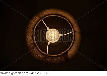 Incandescent Light Bulb In Round Lampshade Glowing In Dark. Extremely Dusty Lamp, Lit Light Bulb On