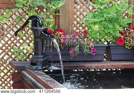 A Water Fountain Infront Of A Lattice With Annuals