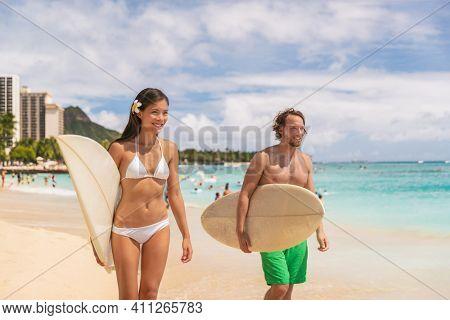 Hawaii Waikiki beach couple tourists surfers happy going surfing. Interracial couple, Asian bikini model woman, Caucasian man walking with surfboards after surf lesson.