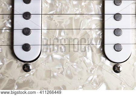Guitar Fretboard With Tuning Pegs And Strings On A Gray Background. Close-up