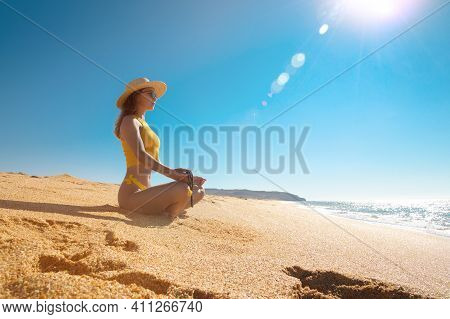 Young Attractive White Woman In A Swimsuit, Sunglasses And A Hat Sits In A Lotus Position On A Sandy
