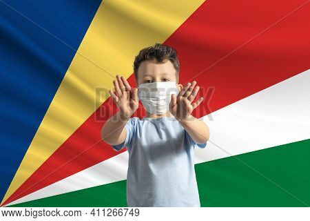 Little White Boy In A Protective Mask On The Background Of The Flag Of Seychelles. Makes A Stop Sign