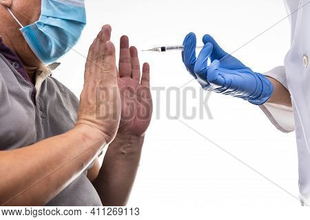 Fearful Worried Middle Age Man Reacting To Medical Practitioner Holding Syringe Loaded With Covid-19
