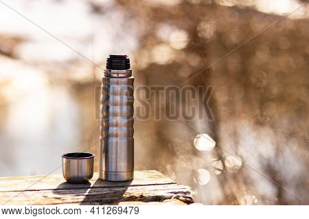 Thermos With Hot Tea. Spring Nature. Thermos On The Background Of The River. Keep Warm In The Spring