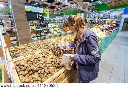 Samara, Russia - September 5, 2017: Young Woman Choosing Fresh Potatoes At Shopping In Chain Hyperma