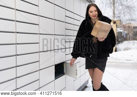 An Attractive Student Collects And Sends A Parcel Via A Parcel Locker In Winter. Automatic Machine F