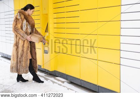 A Wealthy Woman In A Fur Coat Types The Code On The Keypad Of A Parcel Locker. Automatic Machine For