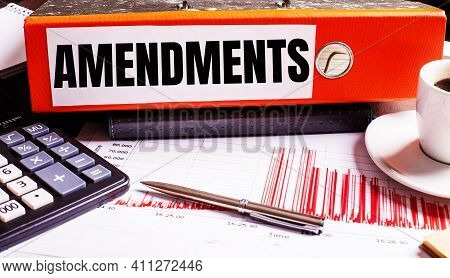 The Red Document Folder Says Amendments Next To The Coffee, Calculator And Pen.