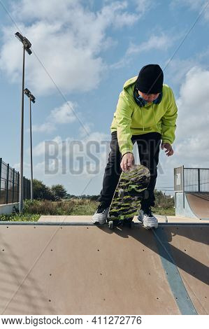 Young, Teenager, With A Skateboard, Holding The Board With The Hand, To Launch Down The Slope, On A