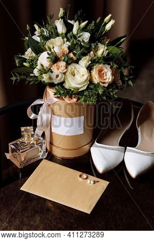 Wedding Accessories On A Wooden Background. White Wedding Shoes. Bridal Bouquet With Pink Flowers An