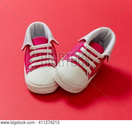 Baby Shoes On Red Color Background, Closeup View