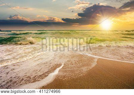 Sea Tide On A Cloudy Sunrise. Green Waves Crashing Golden Sandy Beach In Morning Light. Storm Weathe
