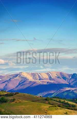 Mountainous Rural Landscape In Springtime. Beautiful Scenery Beneath A Sky With Clouds. Grass Covere