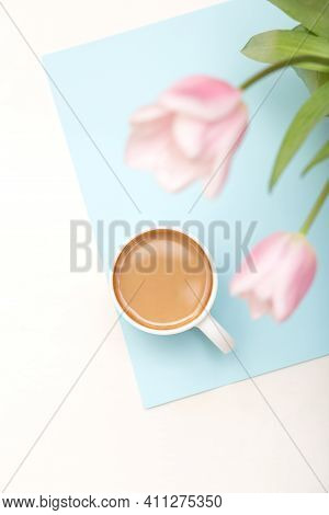Cup Of Coffee And Pink Flowers On Blue And White Pastel Background Top View, Spring Morning Coffee B