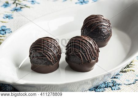 Chocolate Truffles In White Plate On Light Background Table. Homemade Dark Chocolate Truffles.