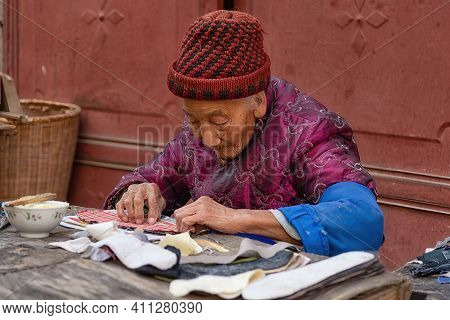 Xizhou, China - April 26, 2019: Portrait Of An Elderly Woman At Work At Xizhou Old Market. She's Wor