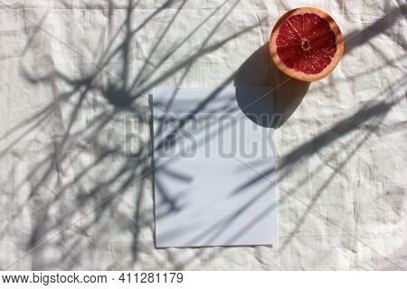 Summer Still Life With Half Of Grapefruit And Blank Paper Card On White Fabric Background. Invitatio