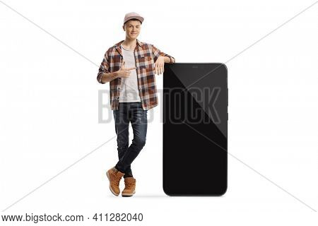 Full length portrait of a young trendy guy posing with a big smartphone and pointing at the screen isolated on white background
