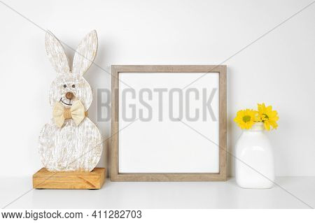 Mock Up Wood Frame With Easter Decor On A White Shelf. Rustic Wood Bunny And Vase Of Spring Flowers.